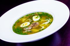 Soup with meat, quail eggs and noodles. In white plate royalty free stock photo
