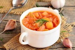 Soup with meat and vegetables in a bowl, spoon, garlic on old wooden background. Soup cooked with meat, potatoes, cabbage, carrots Royalty Free Stock Images