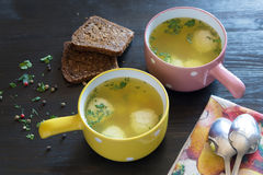 Soup with meatballs in colorful bowl with slices of grain bread Stock Images