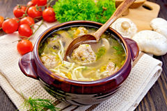 Soup with meatballs and mushrooms in pottery on board Stock Photo