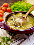 Soup with meatballs and spoon in pottery on napkin Royalty Free Stock Photos