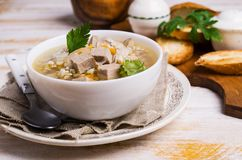 Soup with pearl barley. Meat and vegetables on a wooden background. Selective focus Royalty Free Stock Image
