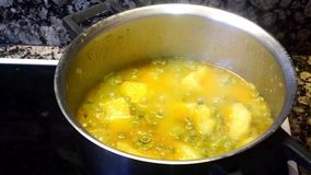 Soup with peas and potatoes boiling in the pot stock footage