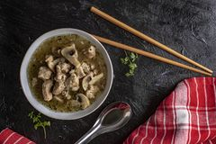 Soup with pieces of pork and mushrooms in bowl stock images