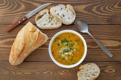 Soup in a plate with slices of bread on a wooden table close-up. Next to the knife and spoon. The concept of proper organic stock photography