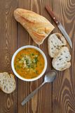 Soup in a plate with slices of bread on a wooden table close-up. Next to the knife and spoon. The concept of proper organic stock image