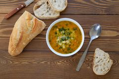 Soup in a plate with slices of bread on a wooden table close-up. Next to the knife and spoon. The concept of proper organic royalty free stock images