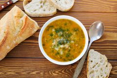 Soup in a plate with slices of bread on a wooden table close-up. Next to the knife and spoon. The concept of proper organic stock photos