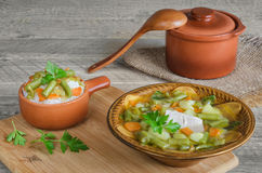 Soup of pork with vegetables and rice, ceramic pot spoon, on wooden background. stock photos