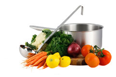 Soup pot, ladle and fresh vegetables. Large soup cooking pot with ladle and fresh vegetables including carrots, cauliflower, squash, onion and tomatoes isolated Royalty Free Stock Photos