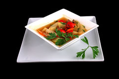 Soup with a potato and vegetables. Soup with a potato, vegetables, greens in a square plate on a black background stock photo