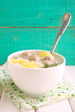 Soup with potatoes, rice and meatballs in a white cup Stock Image