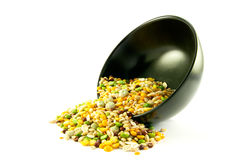 Soup Pulses Spilling from a Bowl. Assorted soup pulses spilling from a round black bowl on a white background Royalty Free Stock Images
