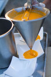 Soup. Pumkin soup being served in kitchen royalty free stock image