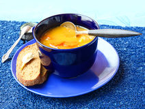 Soup from a pumpkin and carrot in dark blue a soup cup Stock Photography
