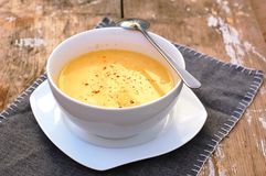 Soup from pumpkin and coconut milk in white bowl with spoon on grey cloth on rustic table Stock Photography