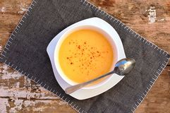 Soup from pumpkin and coconut milk in white bowl with spoon on grey cloth on rustic table Royalty Free Stock Images