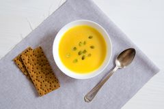 Soup of pumpkin and sunflower seeds in a white plate with a silver spoon and bread on a linen napkin. Royalty Free Stock Photography