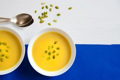 Soup of pumpkin and sunflower seeds in a white plate with silver spoons on a bright background. The concept of healthy eating Royalty Free Stock Photos