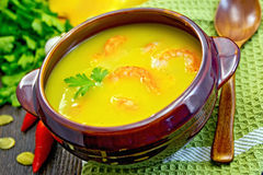 Soup-puree pumpkin with shrimps in clay bowl on board Stock Images