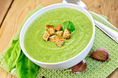 Soup puree of spinach with garlic on board Stock Photos