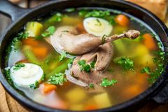 Soup with quail meat, with quail eggs and vegetables royalty free stock photo