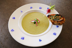 Soup. Radish soup. Cooked from whole plants. Baguette with herbs butter. Plate garnished with some blossoms stock photo