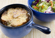 Soup and Salad on Bamboo Mat. A popular meal:  a bowl of French onion soup with bread and browned melted cheese floating on top.  Bowl is a blue onion-soup crock Royalty Free Stock Photos