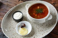 Soup saltwort with lemon, meat, pickles, tomato sauce olives in a bowl on a sacking. Soup saltwort with lemon, meat, pickles, tomato sauce olives in a bowl on a royalty free stock images