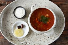 Soup saltwort with lemon, meat, pickles, tomato sauce olives in a bowl on a sacking. Soup saltwort with lemon, meat, pickles, tomato sauce olives in a bowl on a stock photos