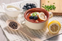 Soup saltwort with meat, potatoes, tomatoes, lemon, black olives. Soup saltwort with meat, smoked sausages, potatoes, tomatoes, marinated pickled cucumber, lemon Royalty Free Stock Image