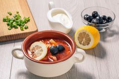 Soup saltwort with meat, potatoes, tomatoes, lemon, black olives. Soup saltwort with meat, smoked sausages, potatoes, tomatoes, marinated pickled cucumber, lemon royalty free stock photography