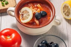 Soup saltwort with meat, potatoes, tomatoes, lemon, black olives. Soup saltwort with meat, smoked sausages, potatoes, tomatoes, marinated pickled cucumber, lemon royalty free stock photos