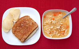 Soup and sandwich. One basic grilled cheese sandwich and potato chips and a large bowl of chicken noodle soup in white over a red tablecloth background Royalty Free Stock Photo
