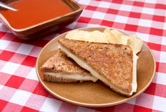 Soup and sandwich. Basic grilled cheese sandwich on toasted bread with chips and a big bowl of tomato soup on a traditional checkered red and white tablecloth Stock Photography