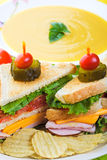 Soup and Sandwich. A delicious clubhouse sandwich, served with crunchy rippled potato chips and creamy butternut squash soup Stock Image