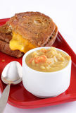 Soup and sandwich. Hearty homemade lunch of thick and chunky yellow split pea soup and grilled cheese on whole grain bread Stock Photos