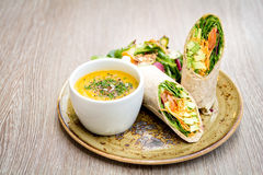 Soup and sandwich wrap. Vegetarian avocado tortilla wrap sandwich and cup of decorated soup on rustic plate Royalty Free Stock Photos