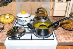 Soup in a saucepan and cooking utensils on a gas stove. In the saucepan with soup ladle. On the stove pan and kettle royalty free stock image