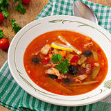 Soup solyanka Russian with meat, olives and gherkins. In bowl Stock Image