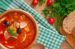 Soup solyanka Russian with meat, olives and gherkins. In wooden bowl Stock Image