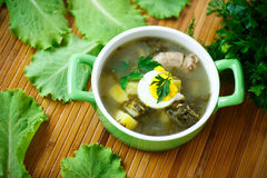 Soup with sorrel. And eggs in a bowl on the table Royalty Free Stock Photography