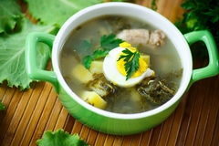 Soup with sorrel. And eggs in a bowl on the table Royalty Free Stock Photo