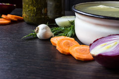 Soup with sorrel, vegetables and boiled egg, red onion, carrots, garlic, dill on dark wooden table. Soup with sorrel, vegetables and boiled egg, red onion Royalty Free Stock Photos