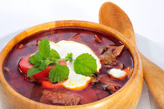 Soup with sour cream. In wood plate with spoon Royalty Free Stock Photos