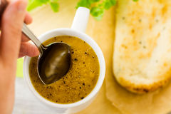 Soup spoon entering mug of soup Royalty Free Stock Images