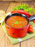 Soup tomato in red bowl on board Stock Photo