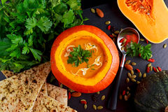 Soup in whole pumpkin with seeds, goji berries, parsley and garlic flat bread for autumn dinner Royalty Free Stock Photo