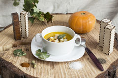 Soup on a wooden background. Soup and pumpkin on a wooden background royalty free stock photography