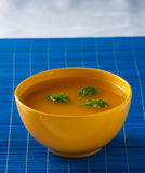 Soup in yellow bowl on the blue pad Royalty Free Stock Photo